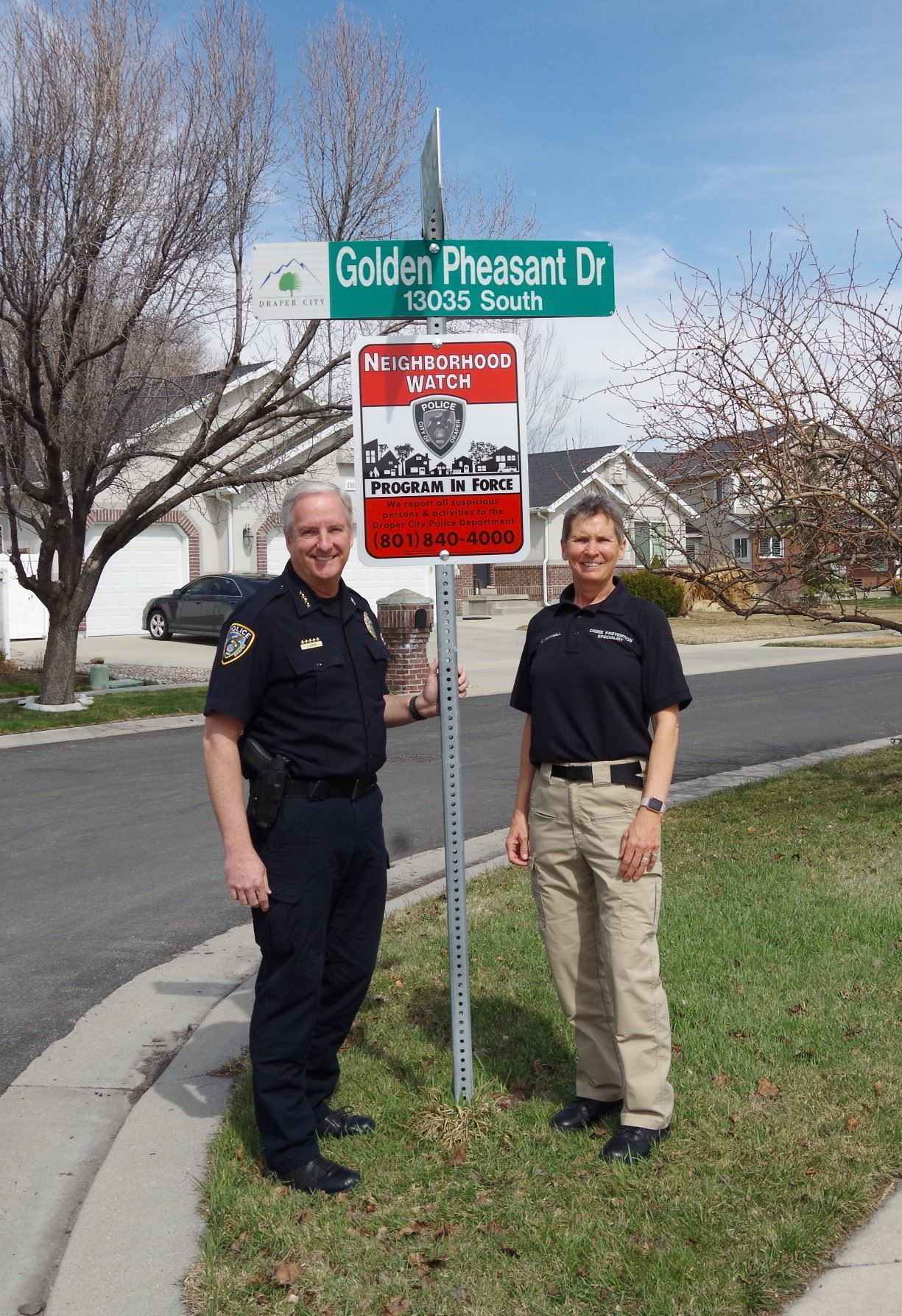 Chief and Crime Prevention Specialist by Neighborhood Watch sign.